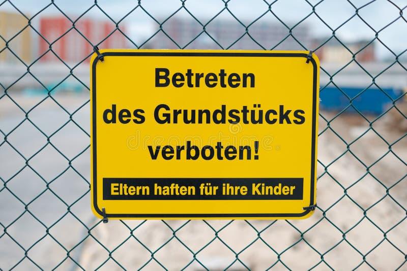在篱芭说的黄色标志:进入被禁止的物产 父母负责他们的儿童德语:Betreten des 免版税图库摄影