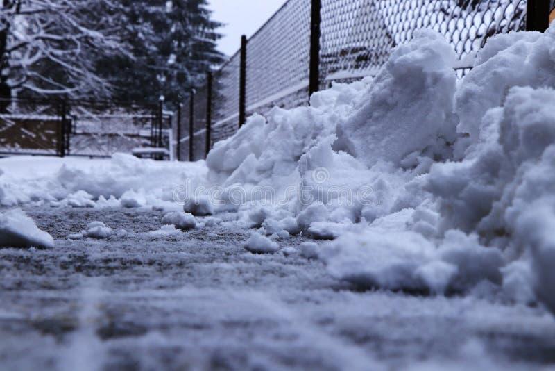 在篱芭附近的雪堆 从车道的尝试的铲起的雪 必须清洗二十厘米雪床罩 库存照片