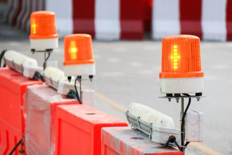 在篱芭,警报器顶部的橙色闪动的和旋转的光与 库存照片