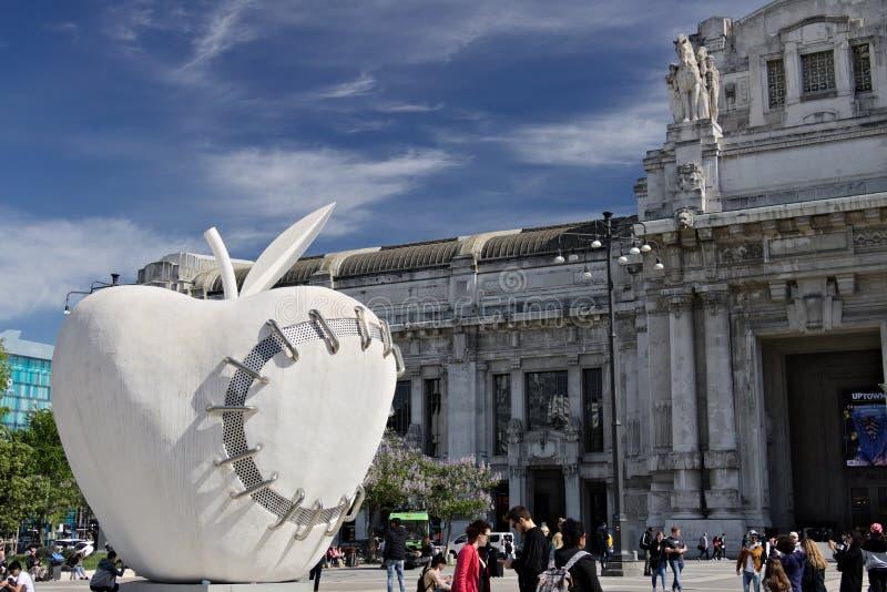 在米兰中央驻地的大苹果 工作在米开朗基罗Pistole旁边 库存照片