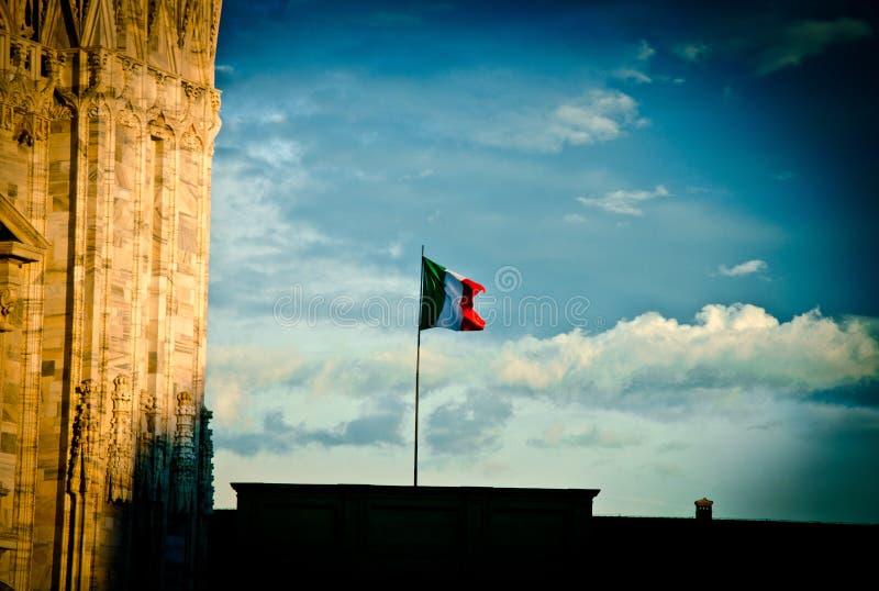 在米兰天空的意大利旗子 库存照片