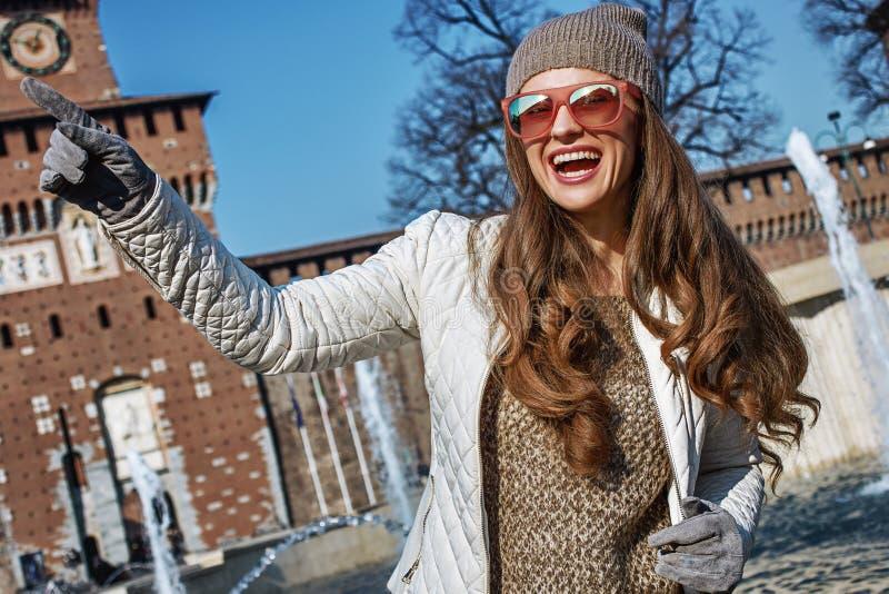 在米兰,意大利指向在某事的愉快的时髦妇女 免版税图库摄影
