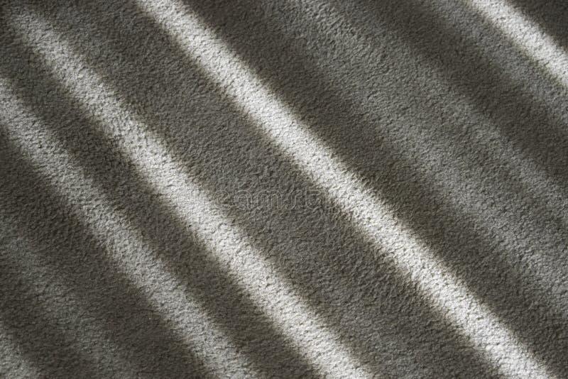 在米黄地毯的对角镶边阴影 图库摄影