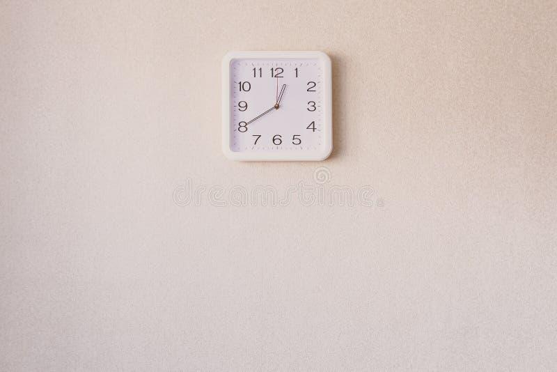 在米黄墙壁上的一个方形的时钟 库存图片