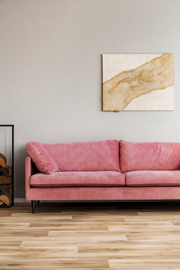在米黄墙壁上的淡色抽象绘画在天鹅绒桃红色长椅后在简单的客厅 库存照片