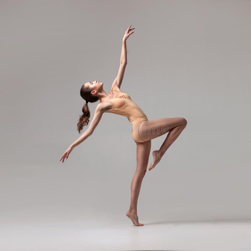 在米黄泳装的年轻美丽的跳芭蕾舞者 免版税库存图片