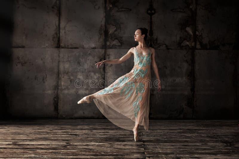 在米黄礼服的年轻美丽的跳芭蕾舞者 图库摄影
