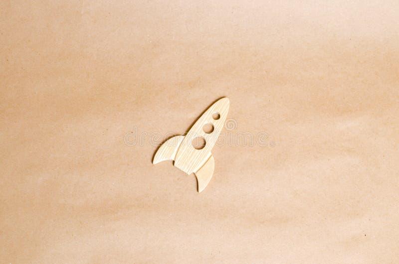 在米黄背景的一枚木火箭 样式减速火箭 空间飞行和成就的概念在高技术 库存图片