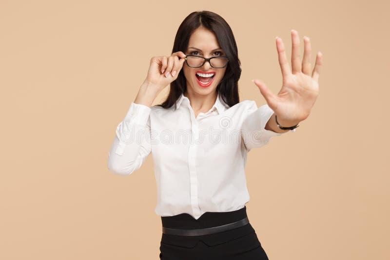 在米黄背景的激动的年轻现代女商人展示中止姿态 成功和优胜者概念 免版税库存图片