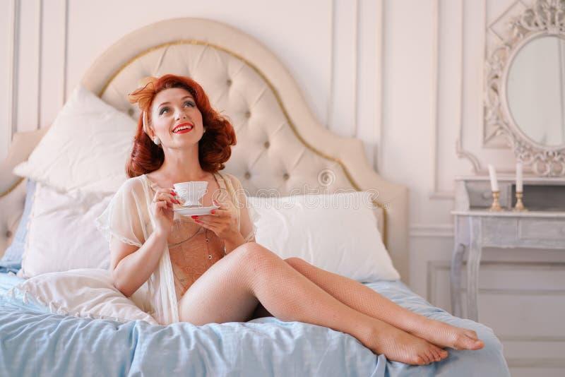 在米黄葡萄酒女用贴身内衣裤打扮的夫人的一个豪华别针摆在她的卧室和食用一个杯子早餐茶 库存照片