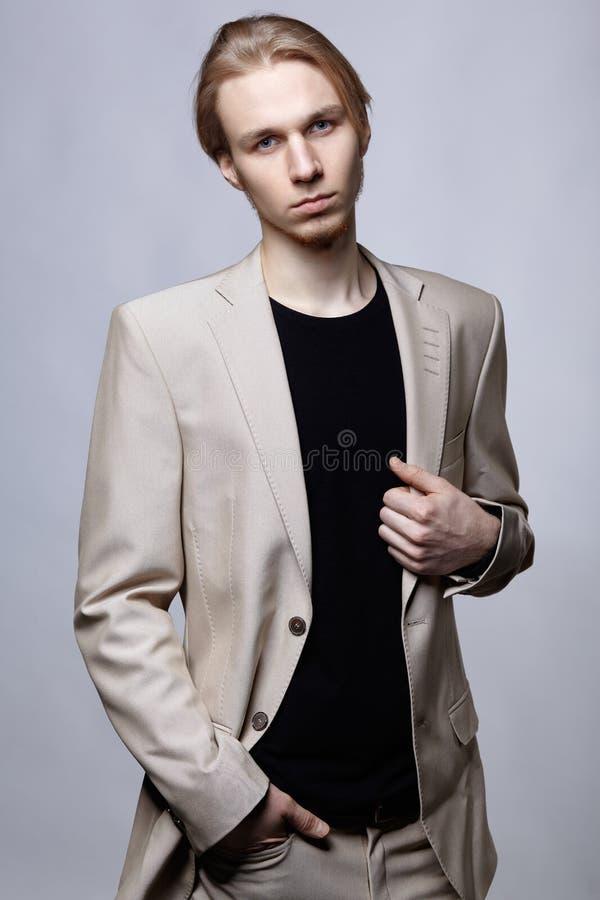在米黄人衣服的年轻白肤金发的男性模型 库存照片