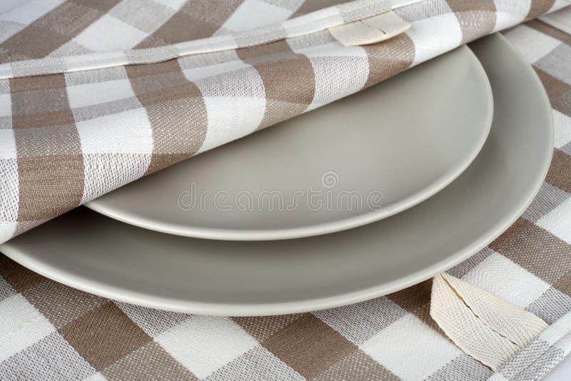 在米黄格子花呢披肩和灰色板材的毛巾 洗碗布和板材 免版税库存照片