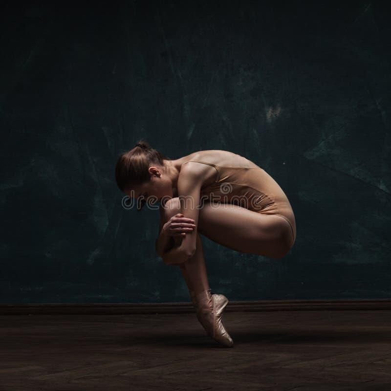 在米黄泳装的年轻美丽的跳芭蕾舞者 库存照片