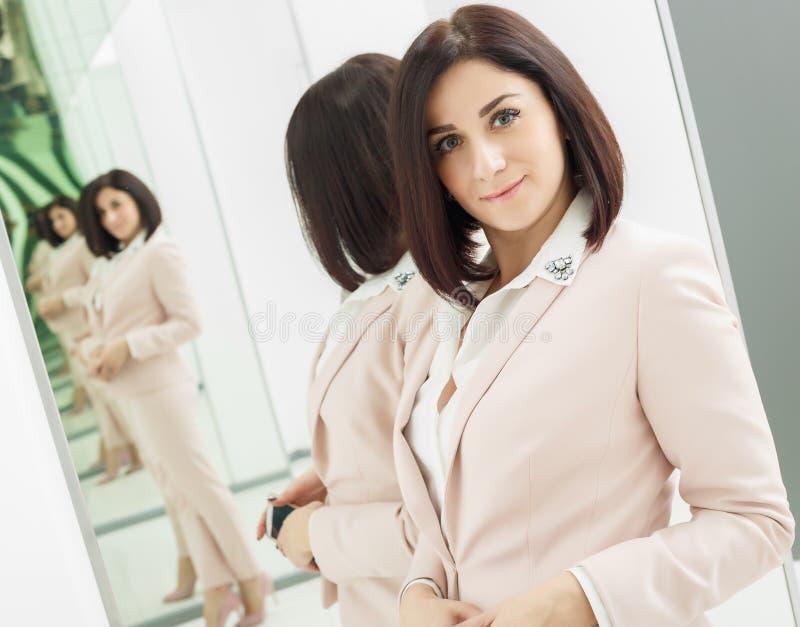 在米黄衣服打扮一名深色头发的可爱的妇女的画象 站立在前面镜子 库存图片