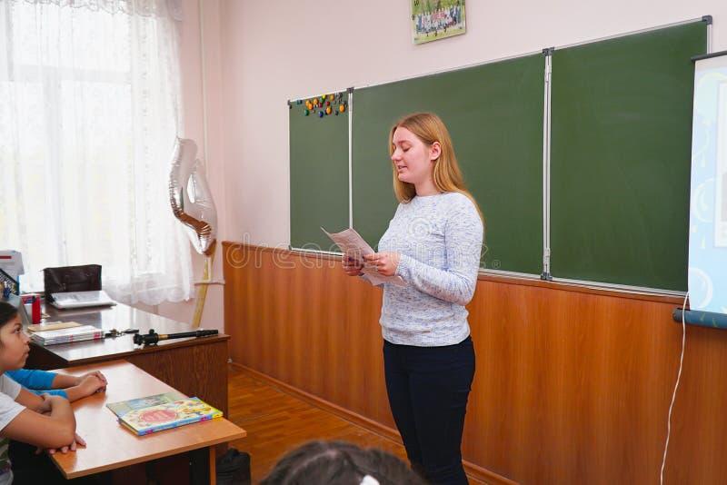 在类前面的年轻老师妇女在黑板 库存照片