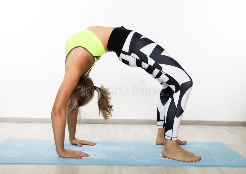 在类的运动的年轻女人实践瑜伽asana 平静的概念和放松 免版税库存照片