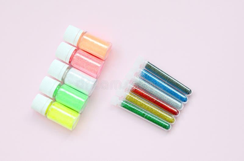 在粉红彩笔背景的五颜六色的闪烁谎言 有多彩多姿的明亮的闪闪发光的许多圆的瓶子指甲油的 免版税库存照片