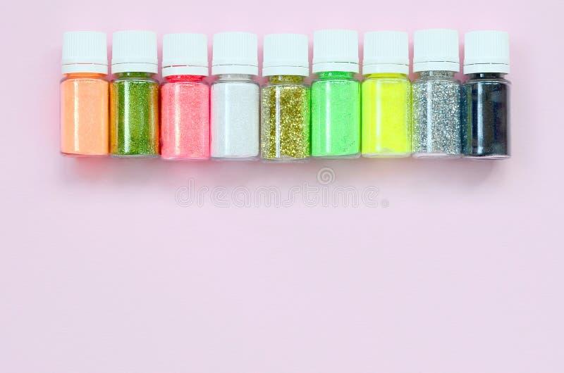 在粉红彩笔背景的五颜六色的闪烁谎言 有多彩多姿的明亮的闪闪发光的许多圆的瓶子指甲油的 库存照片