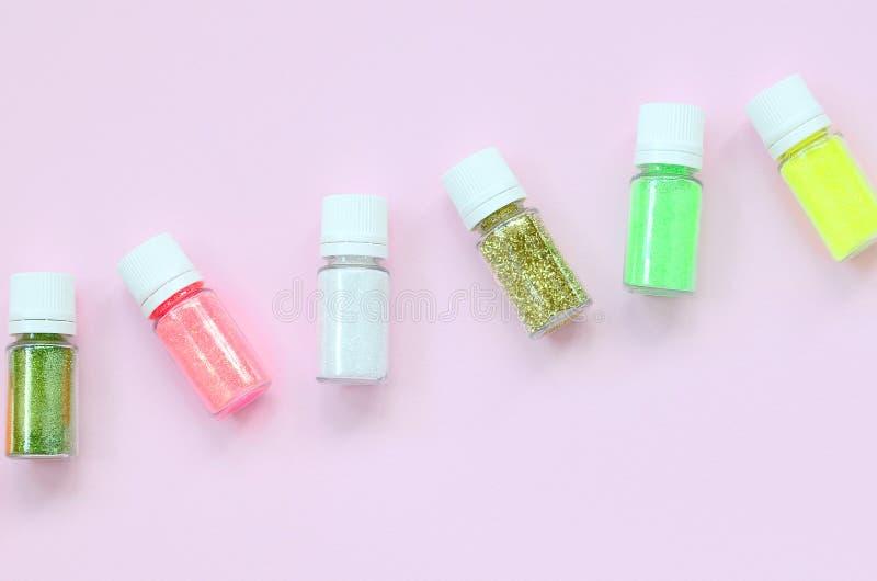 在粉红彩笔背景的五颜六色的闪烁谎言 有多彩多姿的明亮的闪闪发光的许多圆的瓶子指甲油的 免版税库存图片