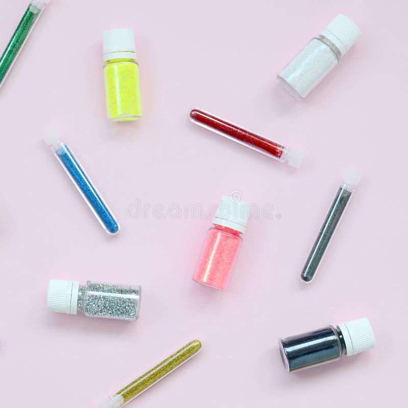 在粉红彩笔背景的五颜六色的闪烁谎言 有多彩多姿的明亮的闪闪发光的许多圆的瓶子指甲油的 免版税图库摄影