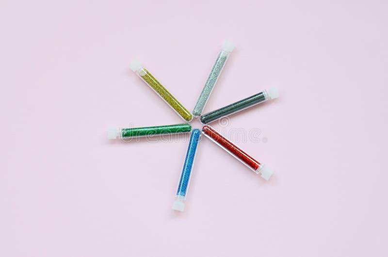在粉红彩笔背景的五颜六色的闪烁谎言 有多彩多姿的明亮的闪闪发光的许多长的瓶指甲油的 库存图片