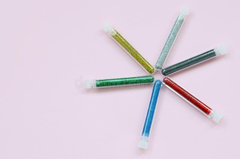在粉红彩笔背景的五颜六色的闪烁谎言 有多彩多姿的明亮的闪闪发光的许多长的瓶指甲油的 免版税库存图片