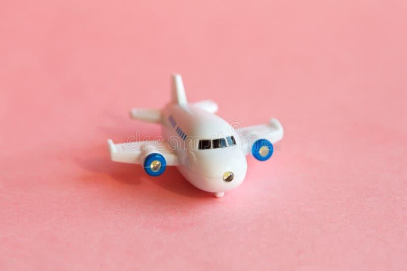 在粉红彩笔背景的微型飞机模型 库存图片