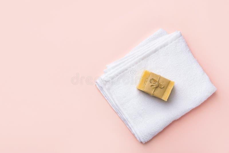 在粉红彩笔背景的被折叠的干净的白蓬松特里毛巾工匠手工制造马赛肥皂 图库摄影