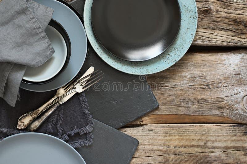 在粗砺的困厄的木桌上的灰色厨房器物 库存图片