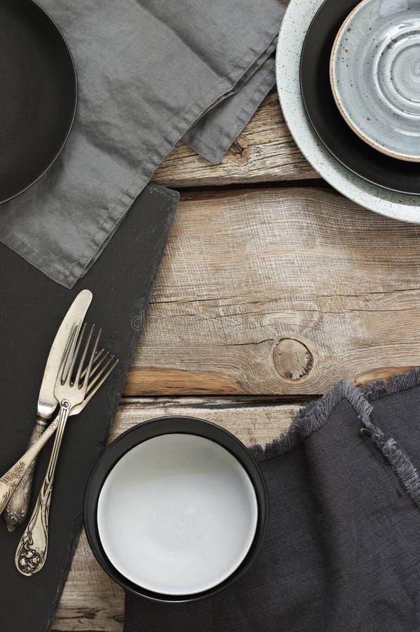 在粗砺的困厄的木桌上的灰色厨房器物 图库摄影