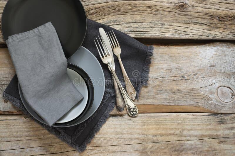 在粗砺的困厄的木桌上的灰色厨房器物 库存照片