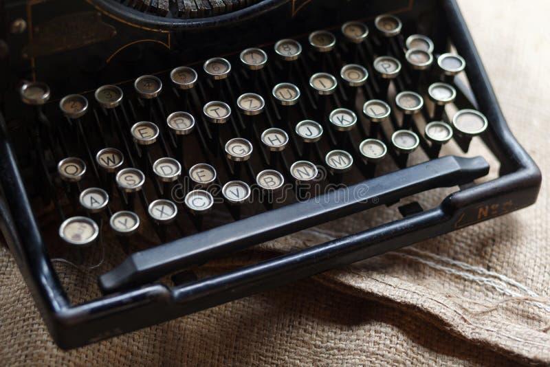 在粗麻布织品的老黑葡萄酒打字机 免版税库存图片