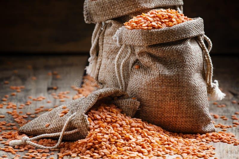 在粗麻布袋的红色小扁豆在老木背景,仍然lif 免版税库存图片