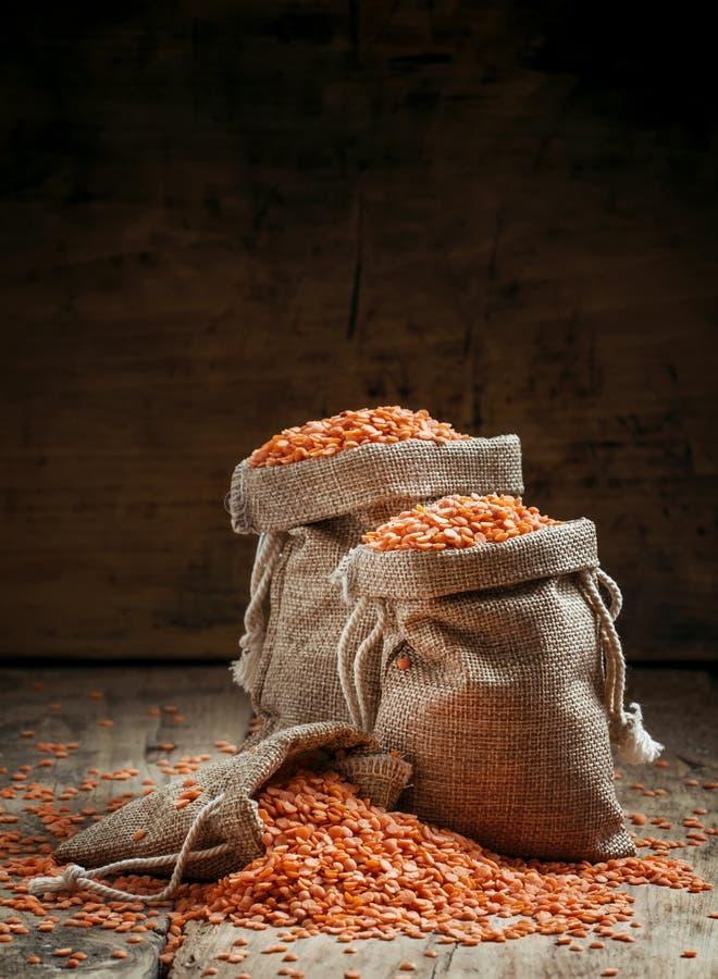 在粗麻布袋的红色小扁豆在老木背景,仍然lif 免版税库存照片