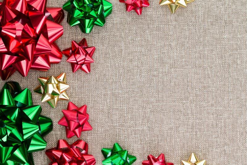 在粗麻布的五颜六色的圣诞节箔弓背景 免版税库存图片