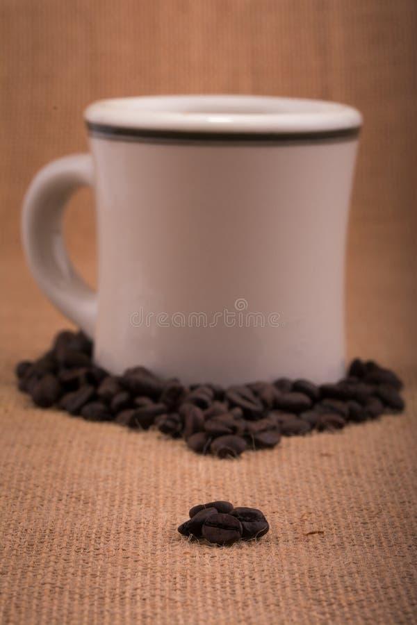 在粗麻布的咖啡豆,与在背景的一个加奶咖啡杯子 图库摄影