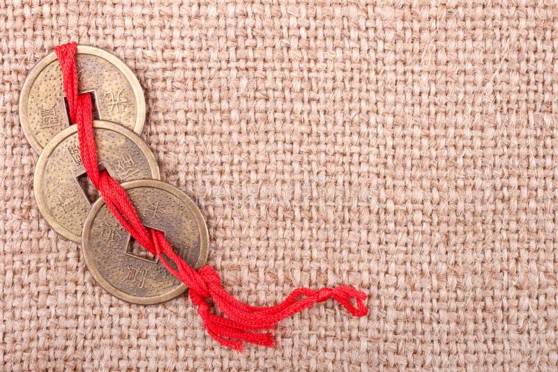在粗麻布背景的中国硬币 免版税库存照片