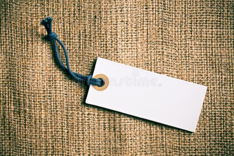 在粗麻布背景的空白的价牌标签 免版税库存照片