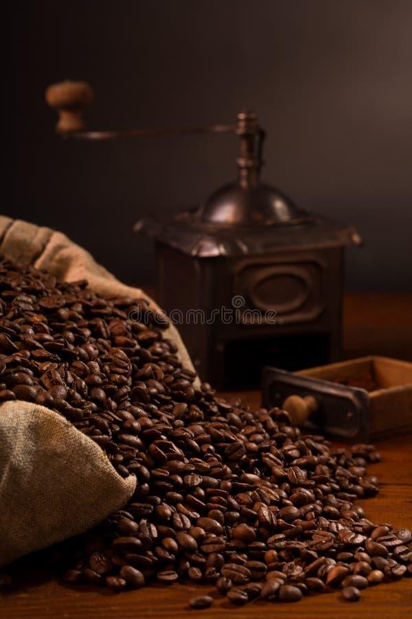 在粗麻布袋的咖啡豆与老研磨机 免版税库存照片