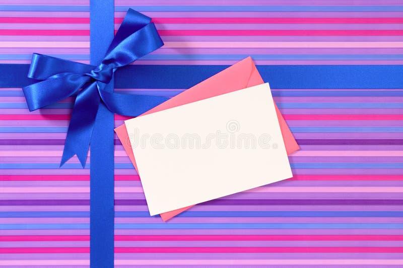 在糖果条纹包装纸、空白的圣诞节或者生日贺卡的蓝色礼物丝带弓与信封 库存照片