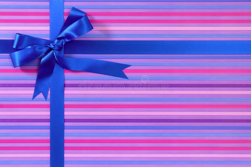 在糖果条纹包装纸背景的蓝色圣诞节或生日礼物丝带弓 免版税库存图片