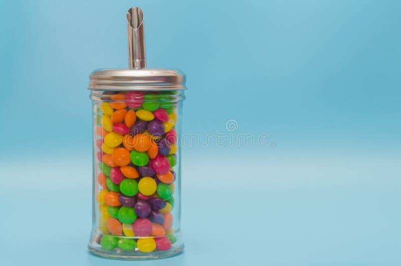 在糖罐,关闭的糖果焦糖-在蓝色背景 图库摄影
