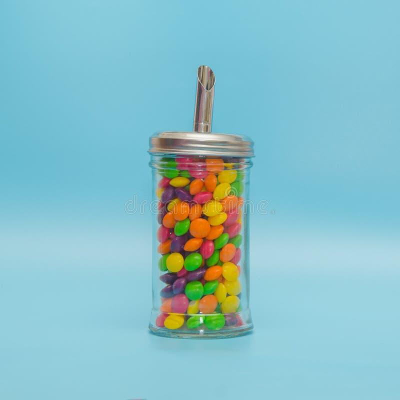 在糖罐,关闭的糖果焦糖-在蓝色背景 库存图片