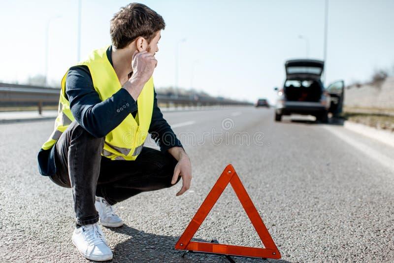 在紧急标志附近的人在路旁 免版税图库摄影