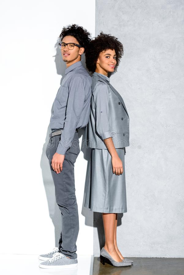 在紧接站立和看在灰色和白色的灰色衣服的年轻非洲amercian微笑的夫妇照相机 库存照片