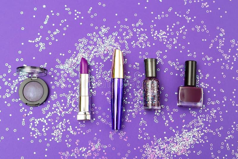 在紫外背景的紫罗兰色化妆用品与在o的衣服饰物之小金属片 免版税库存图片