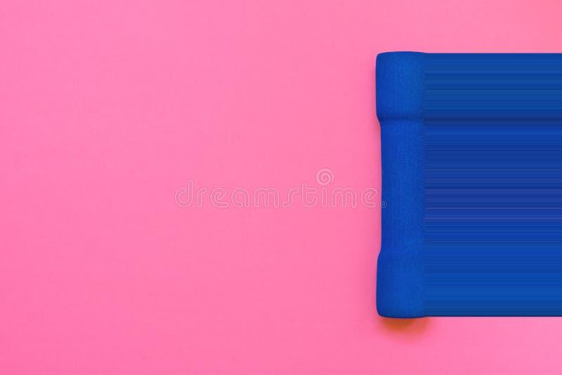 在紫红色的桃红色背景顶视图舱内甲板位置的一个蓝色妇女` s哑铃 映象点舒展小故障动力学模仿 健身能量 库存图片