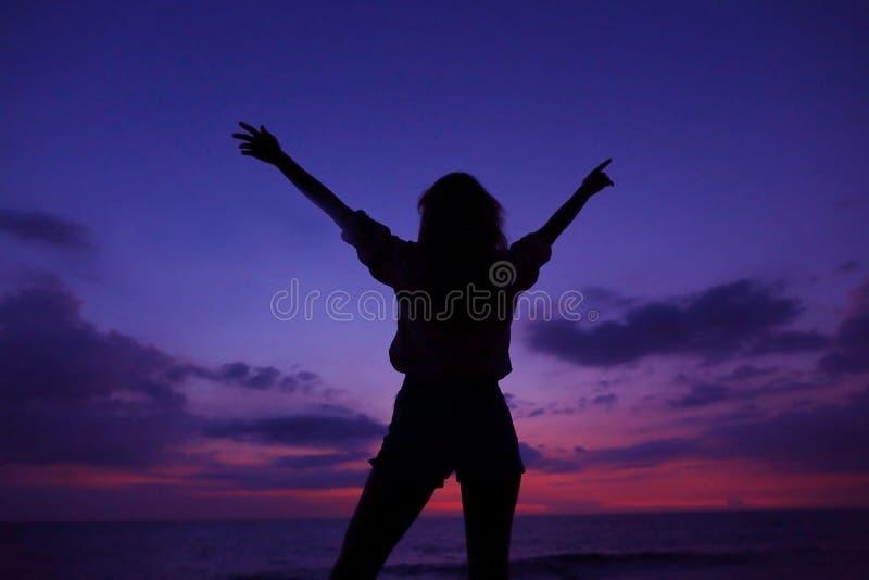 在紫罗兰色日落天空的黑女性剪影与在backround,夏威夷的云彩 免版税库存照片
