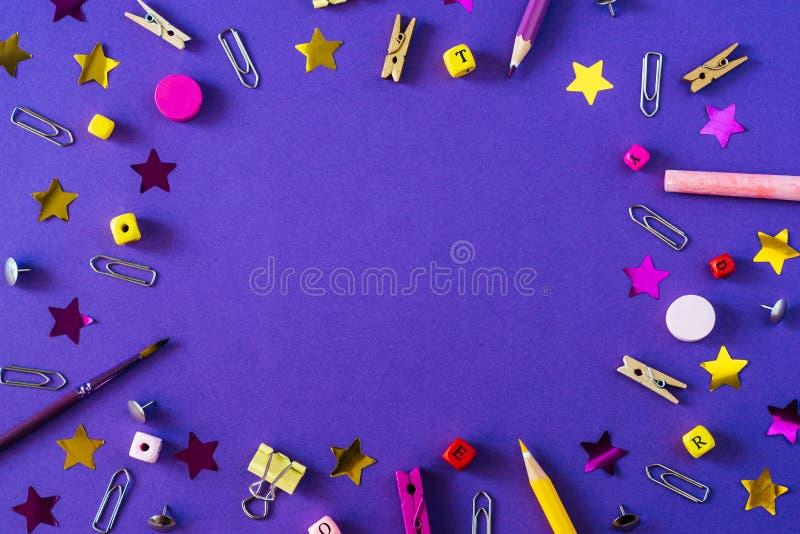 在紫罗兰色背景的多彩多姿的学校用品与拷贝空间 图库摄影