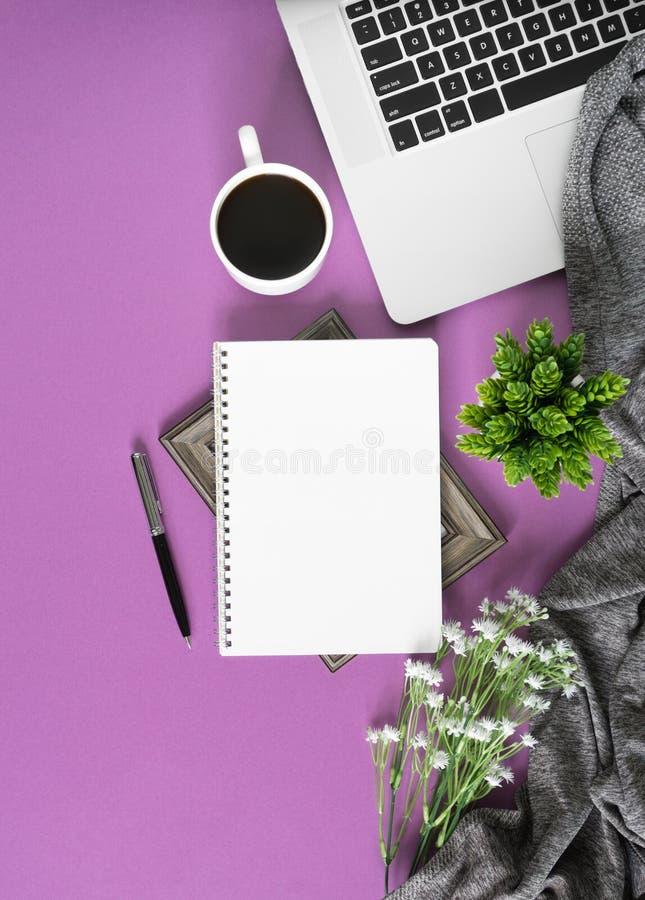 在紫罗兰色背景的家庭办公室工作区 库存图片
